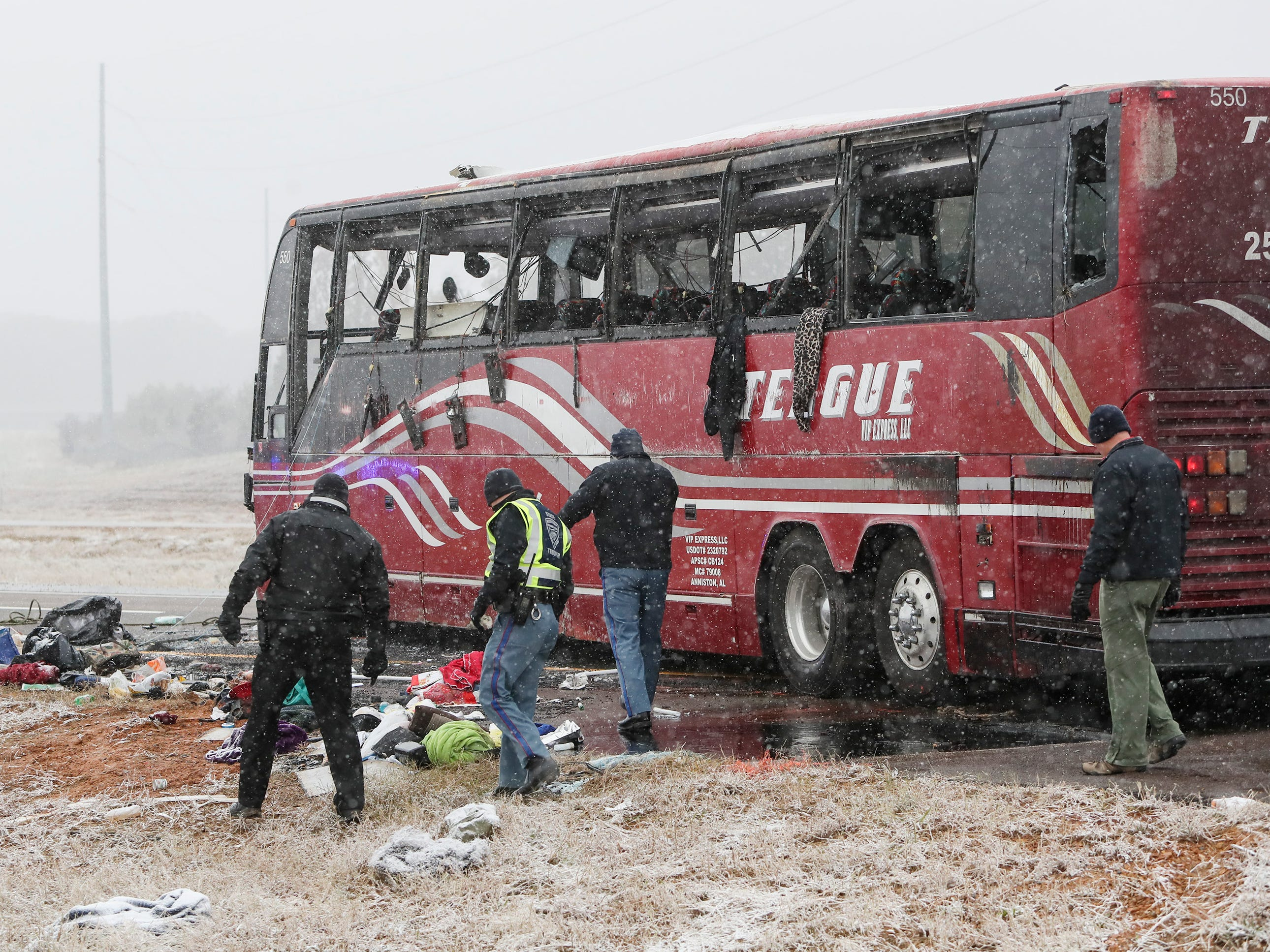 Law enforcement officers inspect the site where a tour bus carrying passengers overturned just after midday, Wednesday, Nov. 14, 2018, in DeSoto County, Miss. The crash came as a winter storm has been raking parts of the South.