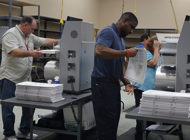 Election workers place ballots into electronic counting machines at the Broward Supervisor of Elections office in Lauderhill, Florida.