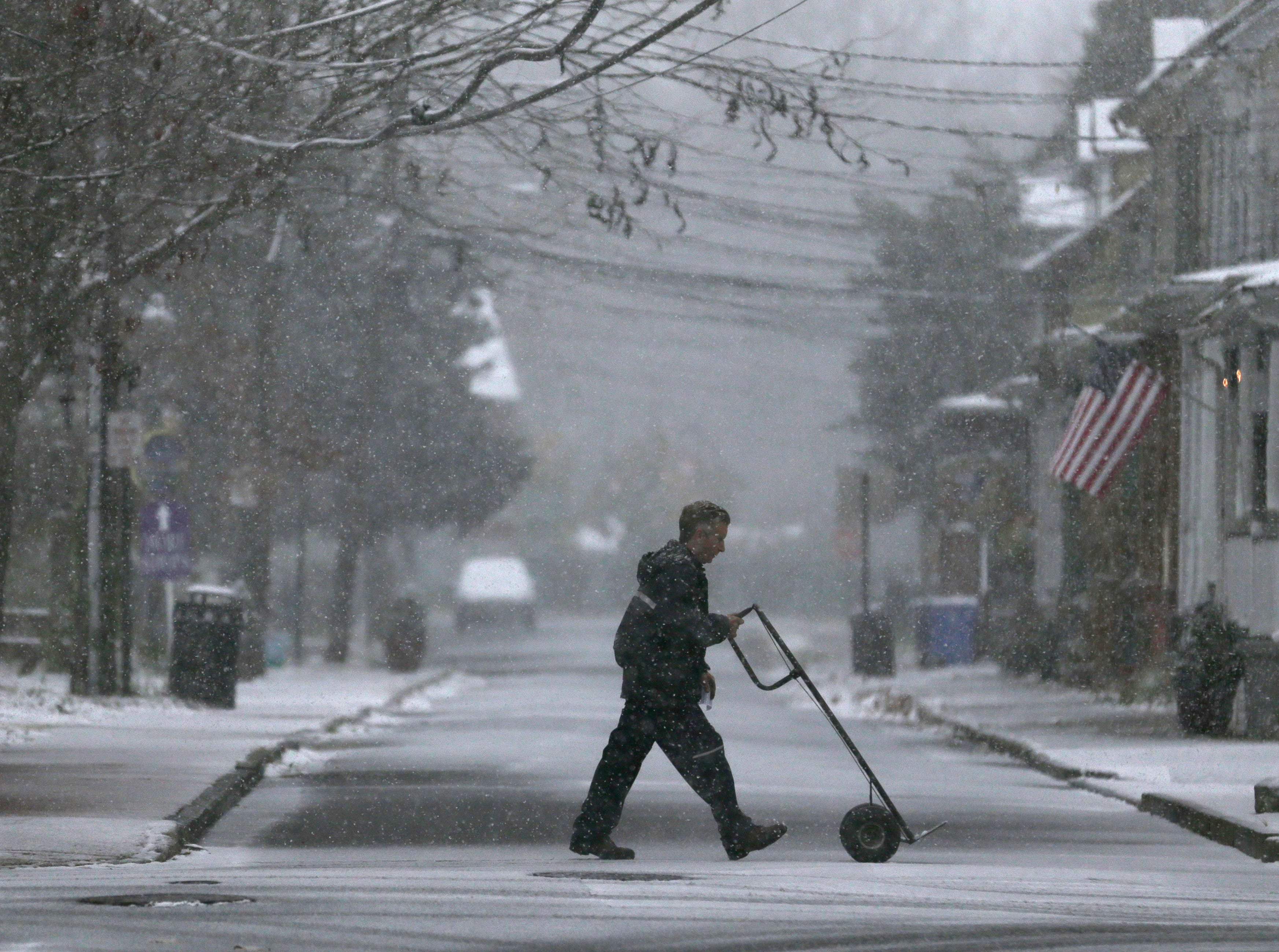 A delivery man makes his way through wintry weather in Mt. Holly, N.J., Thursday, Nov. 15, 2018. New Jerseyans are dealing with their first taste of wintry weather this season. A mix of rain, sleet and snow started falling late Thursday morning in southern areas and was expected to soon move across the state.
