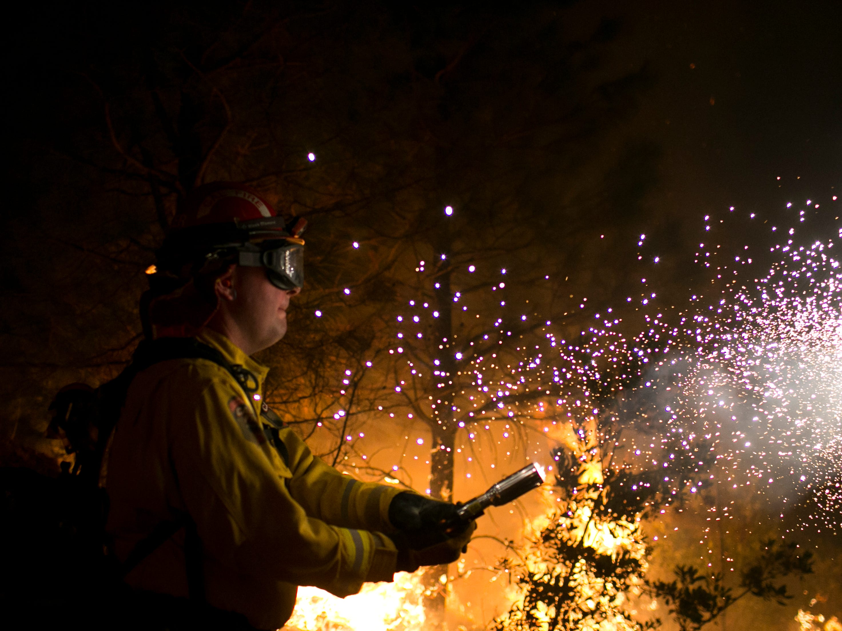 Firefighter Ross Miller fires an incendiary round into a fire line in the Camp Fire as part of a control burn Near Bloomer Hill in Butte County in CalIf. Nov. 14, 2018.