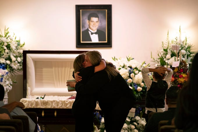 Cheryl Tate, center right, the mother of Cody Coffman, is comforted by a mourner as her son, Chayse, looks at the coffin at a funeral service for Coffman on Nov. 14, 2018, in Camarillo, Calif. The 22-year-old was among a dozen people killed in a Nov. 7, 2018, shooting at a country music bar in Thousand Oaks, Calif.