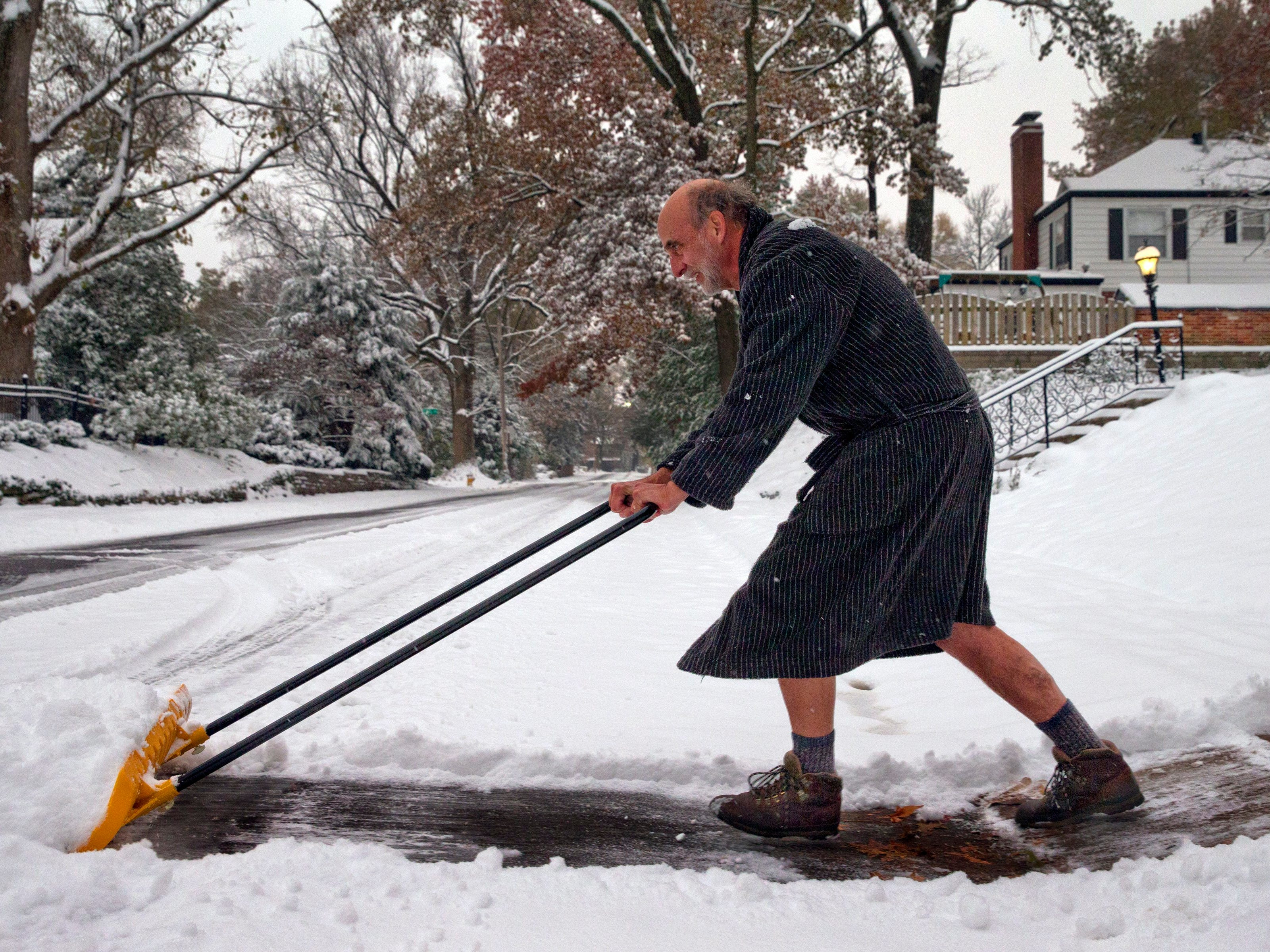 """Richard Burst clears snow from his driveway Thursday, Nov. 15, 2018 in St. Louis. """"All I really need to accomplish are two lanes for my car,"""" he said."""