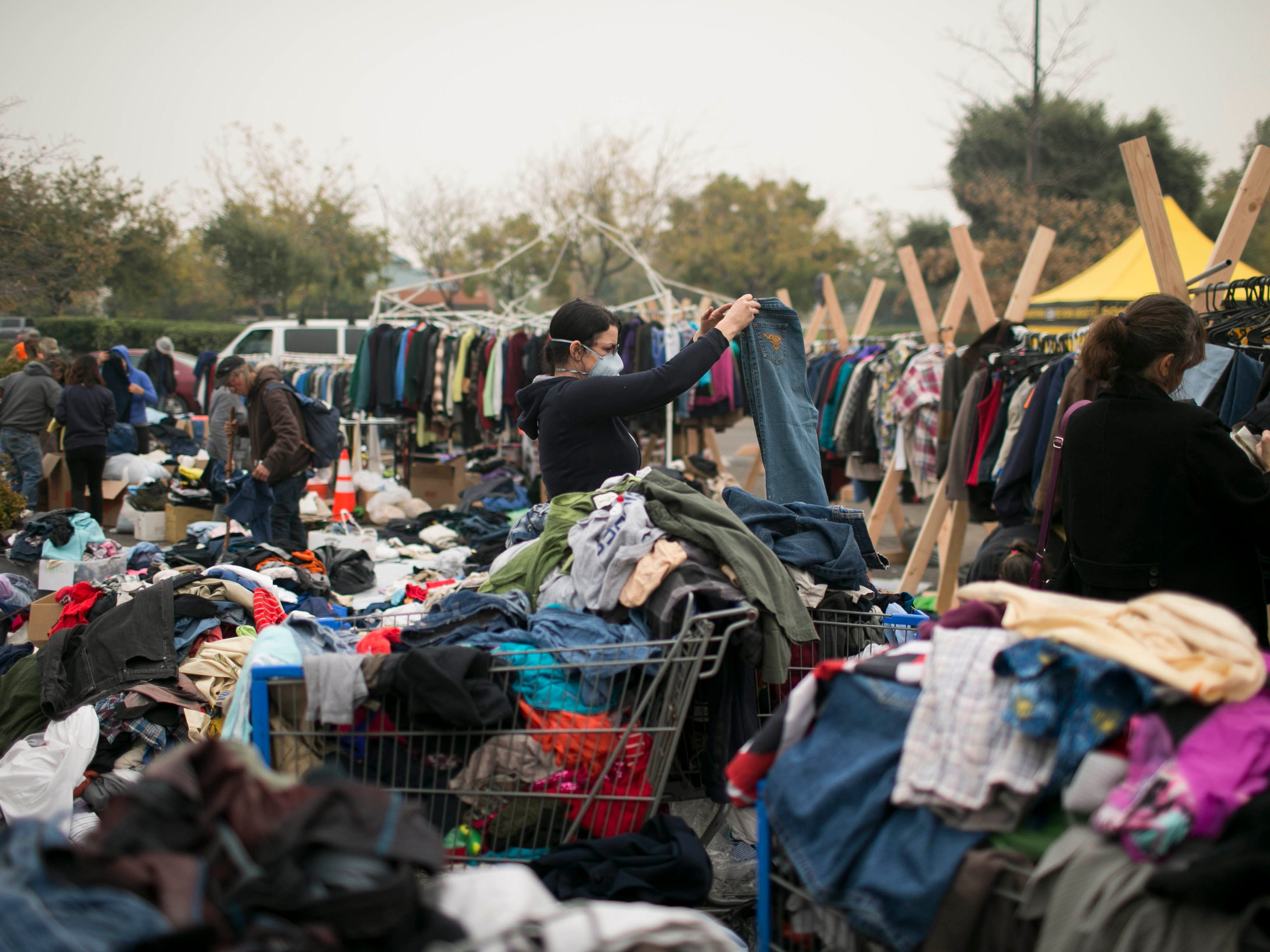 Evacuees from the Camp Fire sort through donated supplies outside a Walmart on Nov. 13, 2018, in Chico, Calif.
