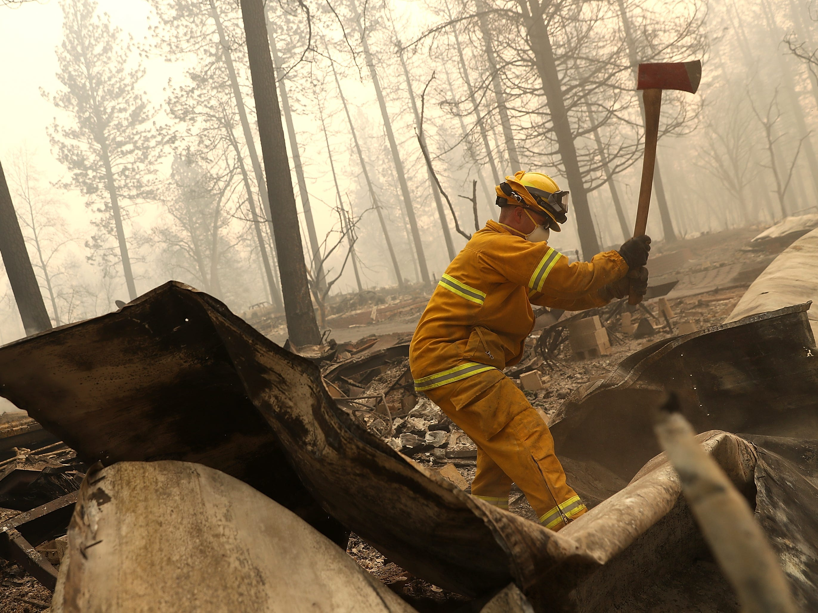A San Francisco firefighter uses an axe to dismantle a burned mobile home as he searches for human remains at a mobile home park that was destroyed by the Camp Fire on Nov. 14, 2018 in Paradise, Calif.