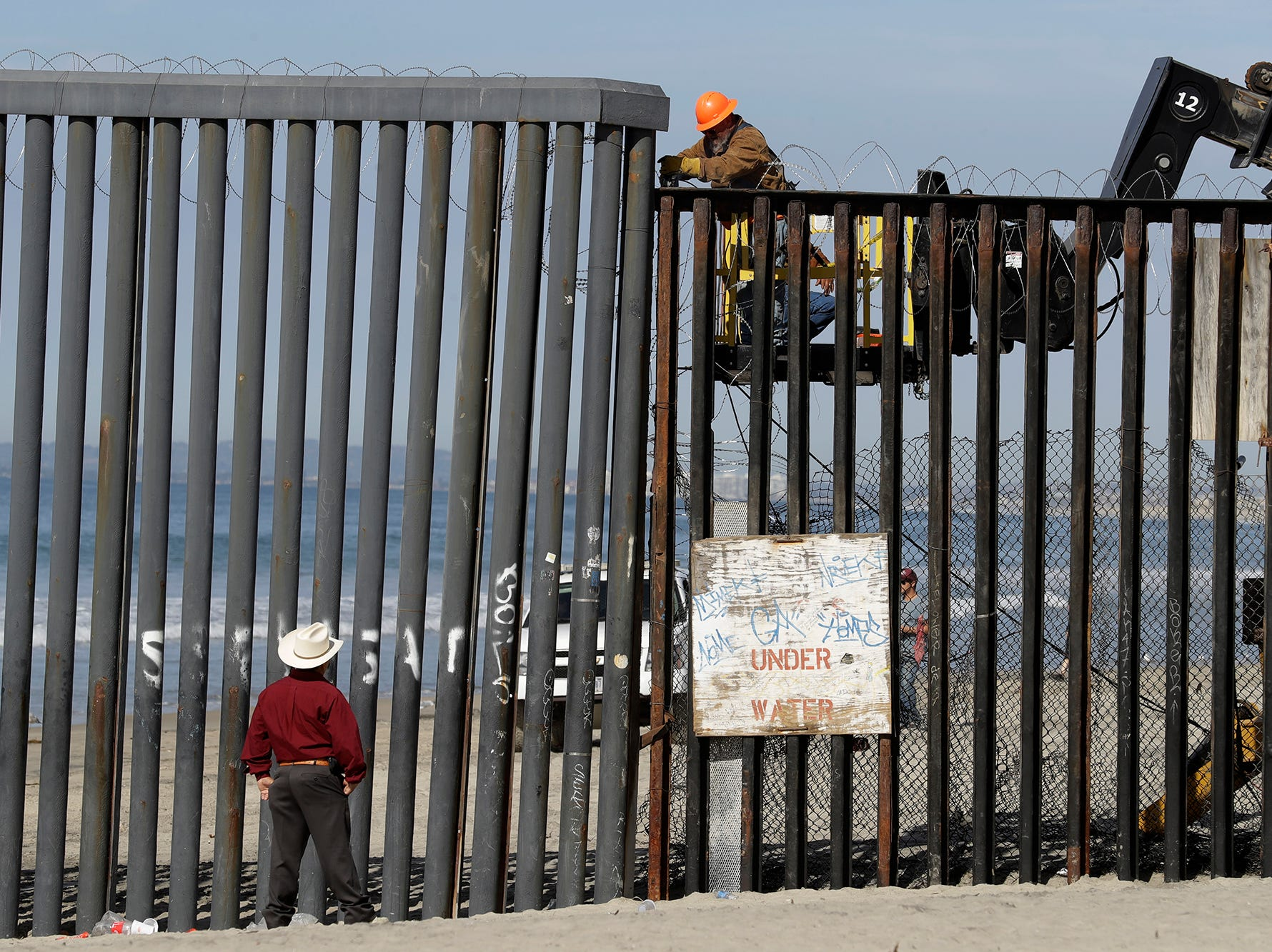 A man on the U.S. side of the border, top, works on the border structure as a man looks on, at the beach seen from Tijuana, Mexico, Thursday, Nov. 15, 2018.