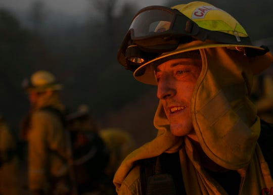 Firefighter Brandon Feller looks into a control burn used to help fight the Camp Fire Near Bloomer Hill in Butte County in Calif. Nov. 14. 2018. Feller was burned in a fire earlier in the year and after being cleared for medical leave returned to work at the Camp Fire.