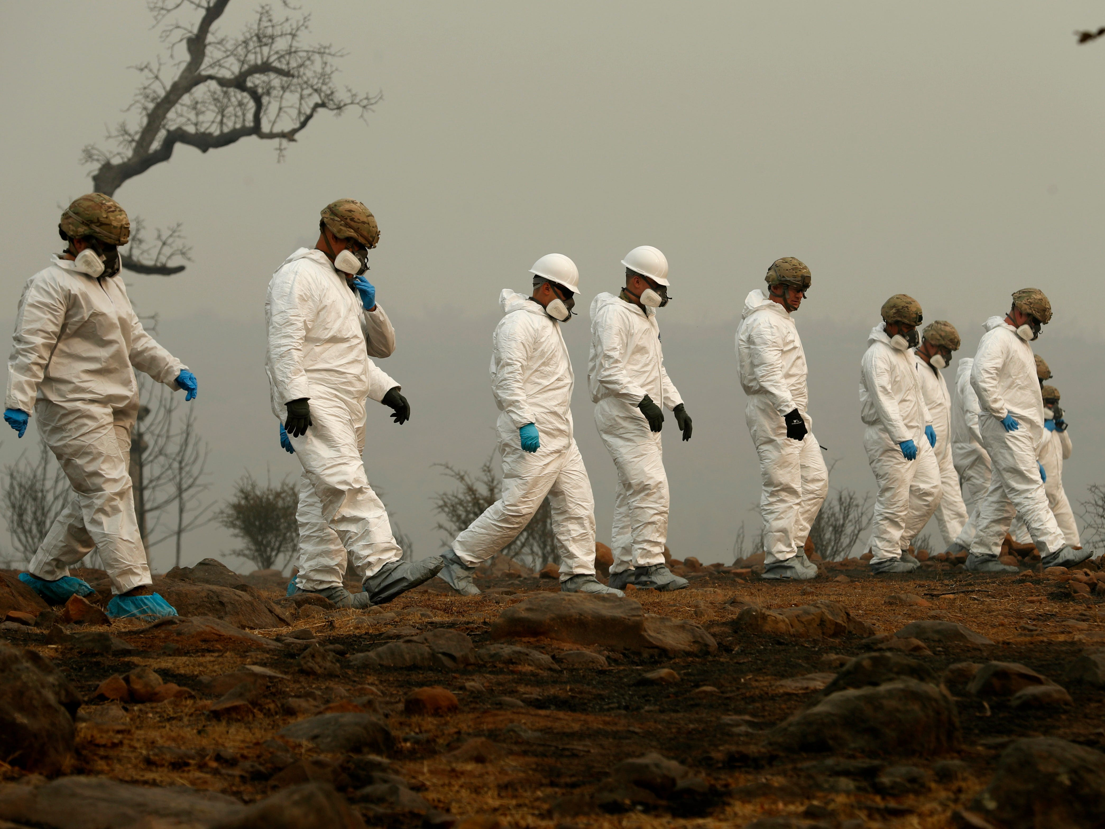 Members of the California Army National Guard search a property for human remains from the Camp Fire on Nov. 14, 2018, in Paradise, Calif.