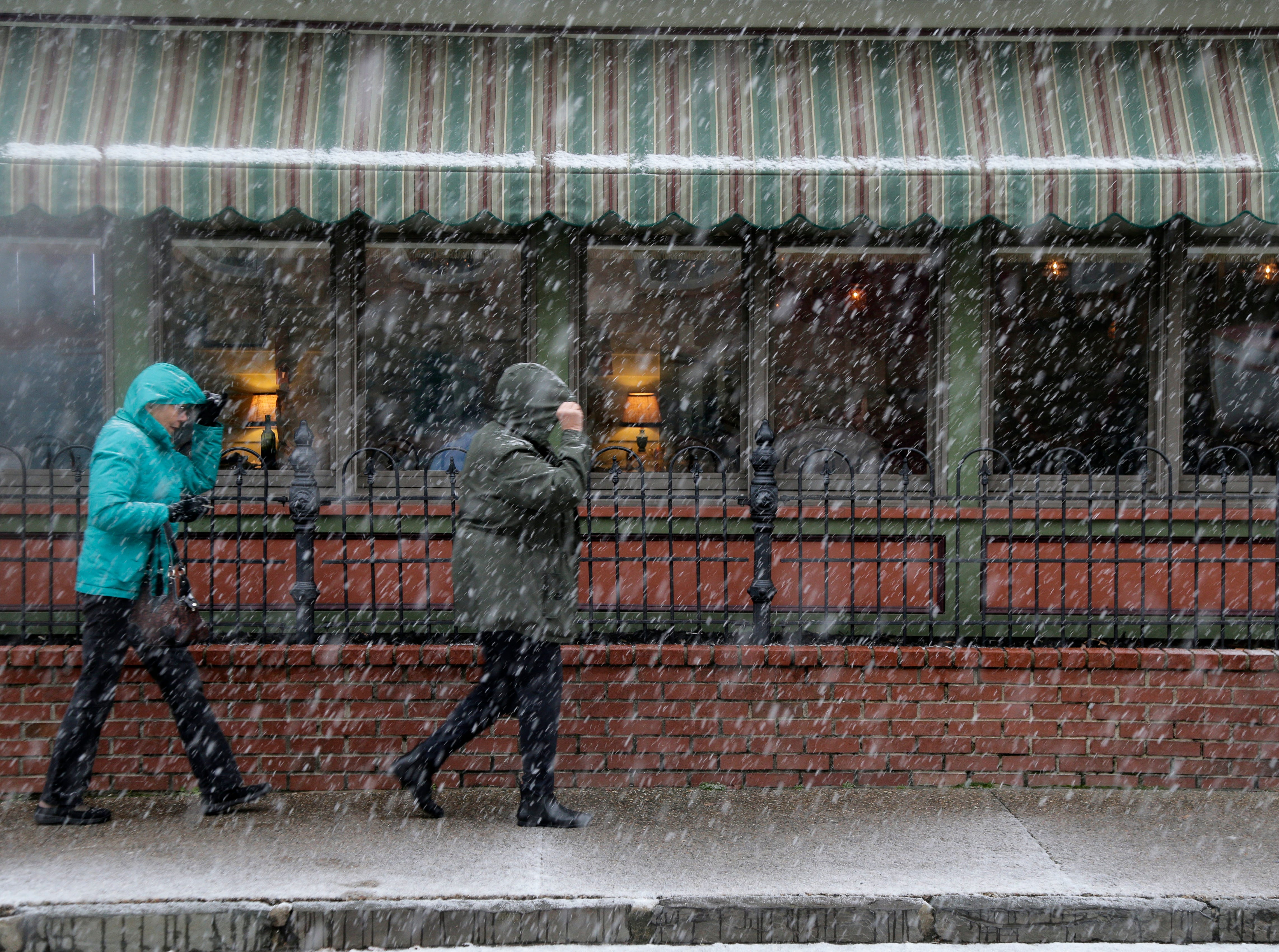 Pedestrians make their way through wintry weather in Mt. Holly, N.J., Thursday, Nov. 15, 2018.   A mix of rain, sleet and snow started falling late Thursday morning in southern areas and was expected to soon move across the state.