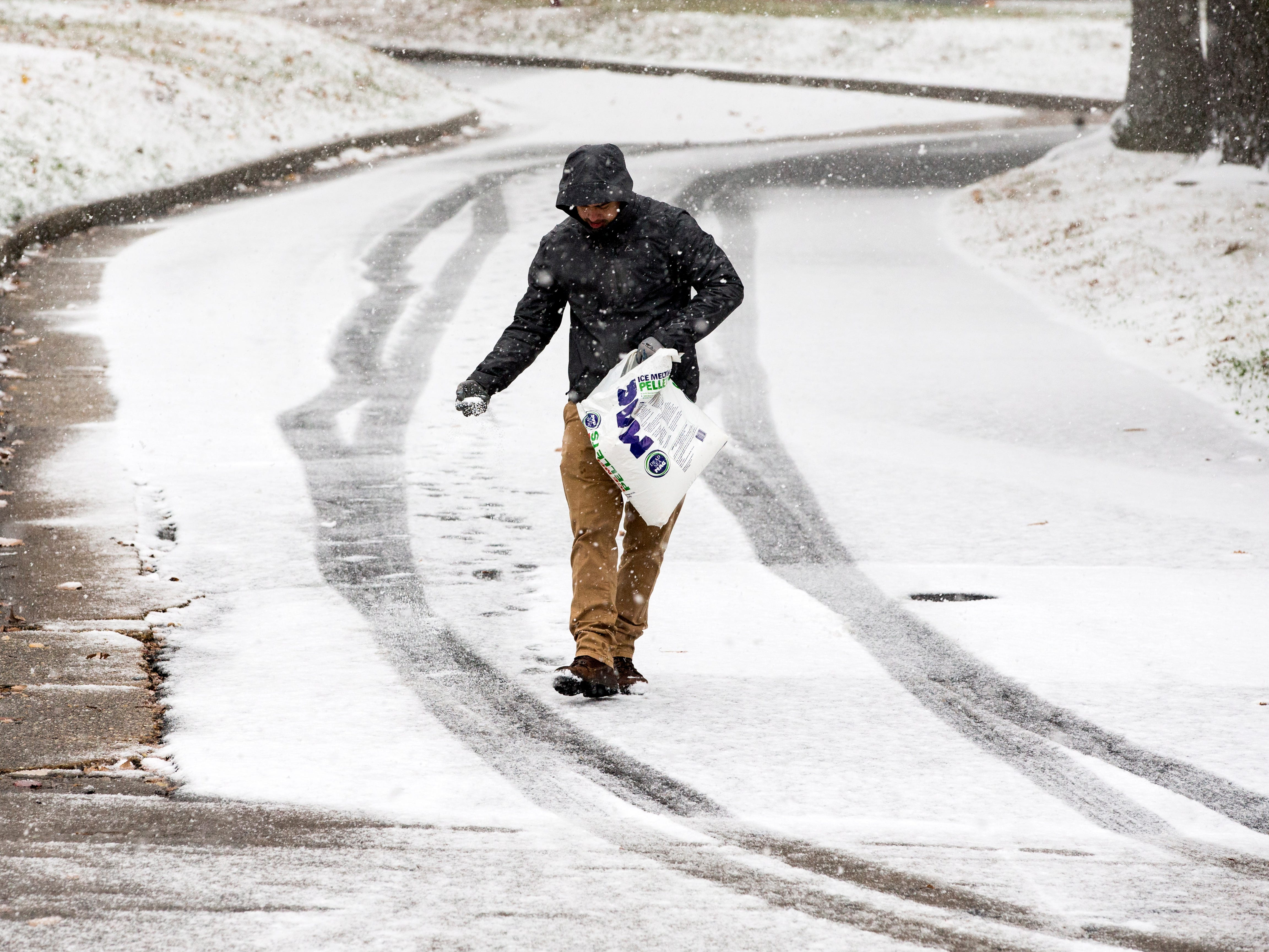 A man throws salt on a road beside Saint John Paul II Seminary, during this season's first snowfall in Washington, D.C., Nov. 15, 2018.