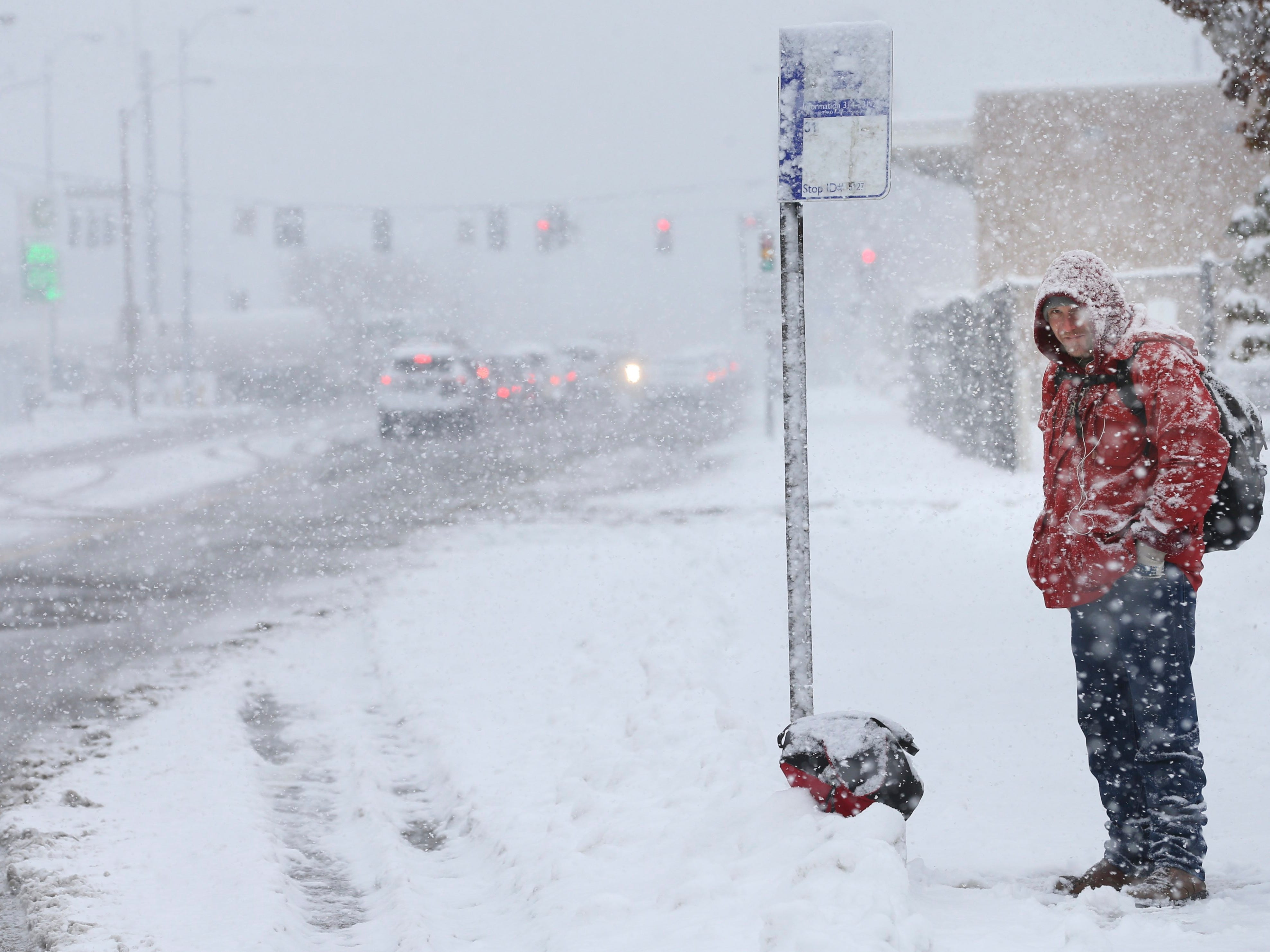 Lyod Graham waits for the bus during a snowstorm in St. Louis, Mo., Thursday, Nov. 15, 2018.