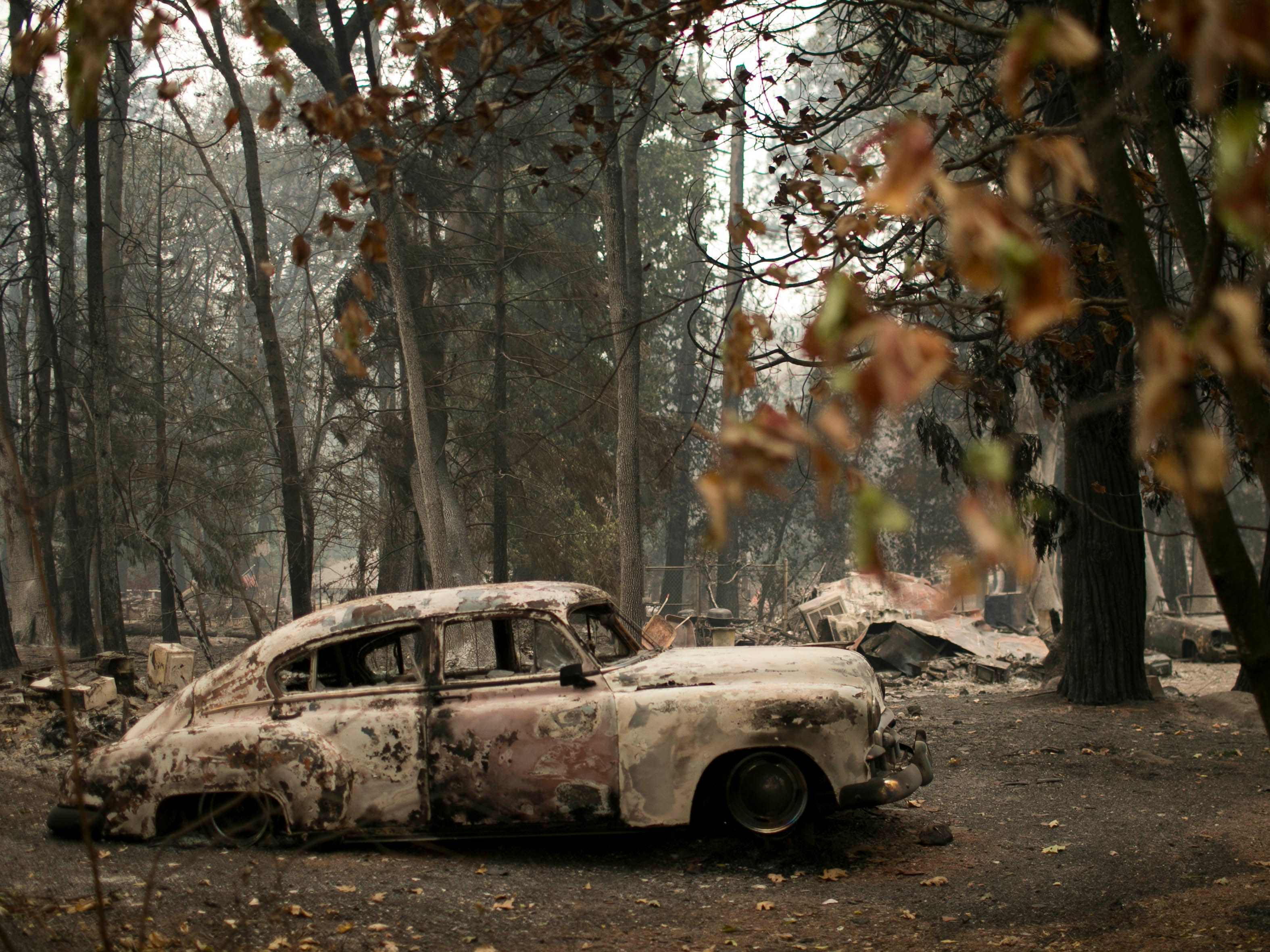 A burned vehicle sits beside a property destroyed by the Camp Fire on Nov. 13, 2018, in Magalia, Calif.