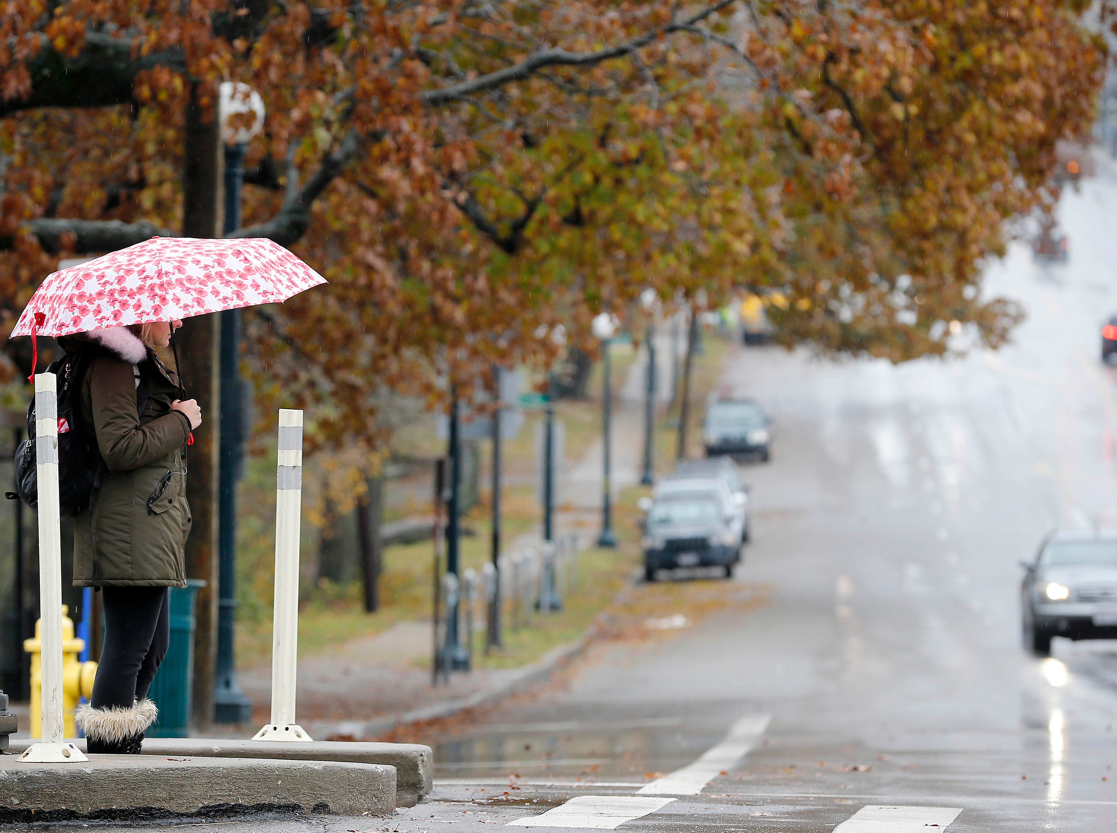 A woman waits to cross Clifton and Dixmyth Ludlow Avenues Thursday, Nov. 15, 2018, as the rain the rain continues to fall. An overnight ice storm caused downed power lines and trees. According to Duke Energy, 102,267 customers were without power in the region Thursday morning.