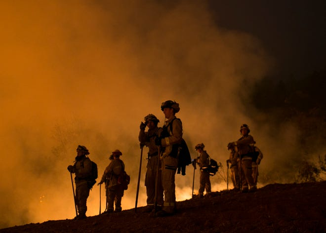 Firefighters hold a line in the Camp Fire with a control burn Near Bloomer Hill in Butte County in Calif. on Nov. 14, 2018.