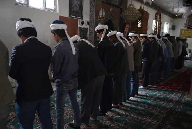 In this file photo taken on April 16, 2015, Uighur men are seen praying in a mosque in Hotan, in China's western Xinjiang region.