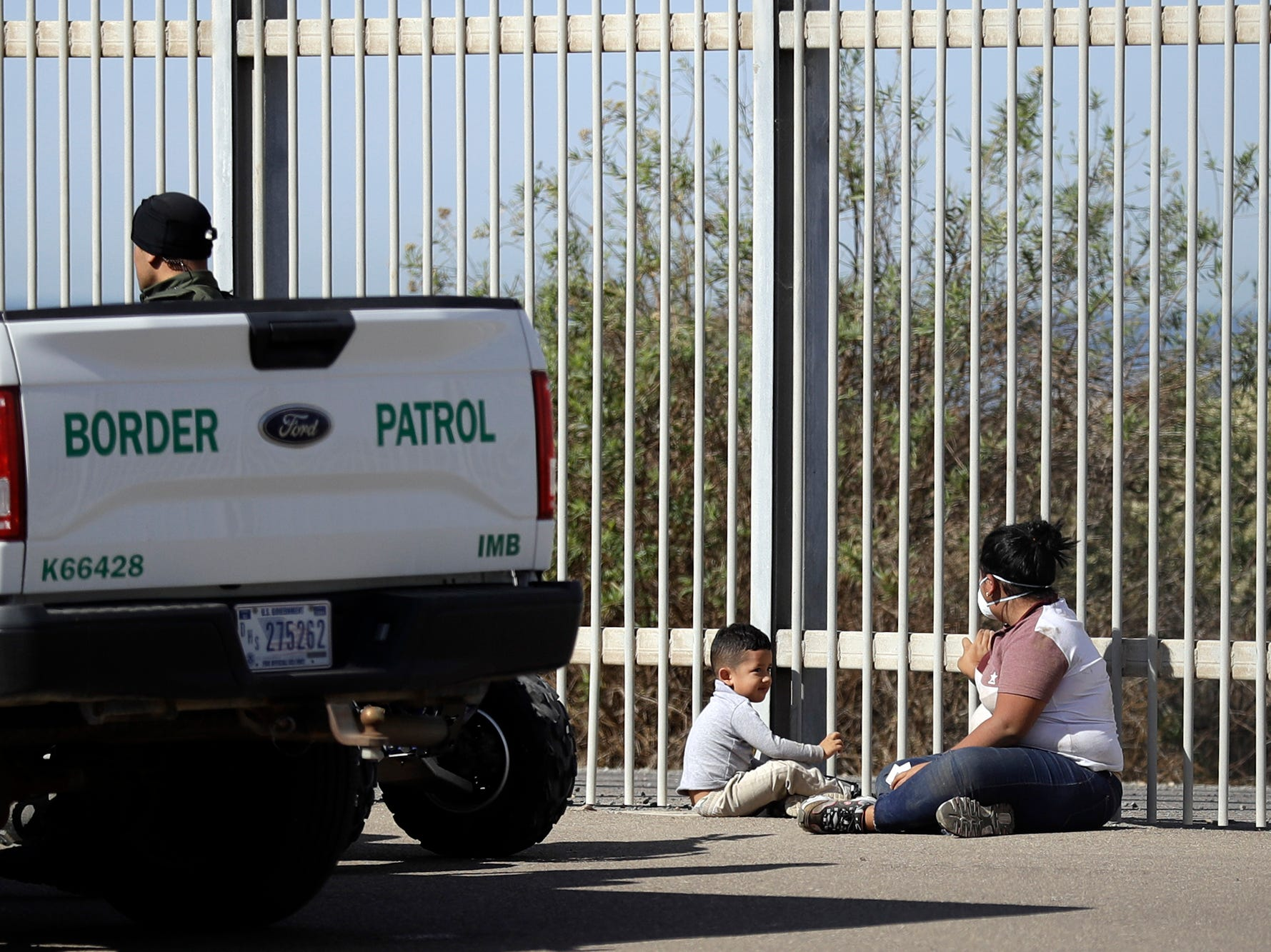 A woman and child are detained by U.S. Border Patrol agents as they sit between two border structures located on the U.S. side, seen from Tijuana, Mexico, Thursday, Nov. 15, 2018. It is unknown if the two are members of a migrant caravan, but migrants from a first of three caravans continue to arrive by the hundreds in Tijuana.
