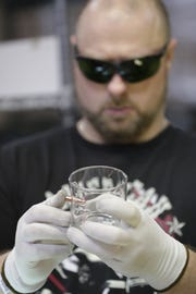 Anthony Pontone works to place a bullet into a glass Friday at BenShot, a small business in Hortonville.