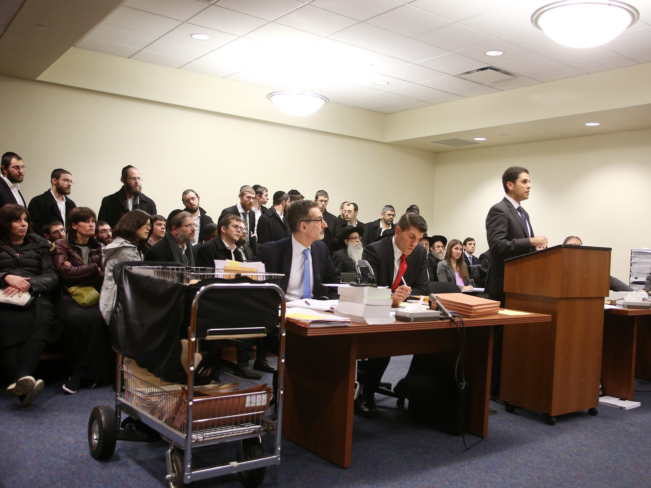 A large crowd fills the courtroom as Rabbi Osher Eisemann, founder of Lakewood's School for Children with Hidden Intelligence and who is facing criminal charges alleging misuse of public money, appears before Judge Benjamin Bucca at the Middlesex County Courthouse in New Brunswick, NJ Friday, November 16, 2018.  His lawyer, (PICTURED ON RIGHT STANDING) Lee Vartan, is arguing the indictment should be dismissed because an amount equal to the taxpayer dollars allotted to the school was spent on legitimate purchases.