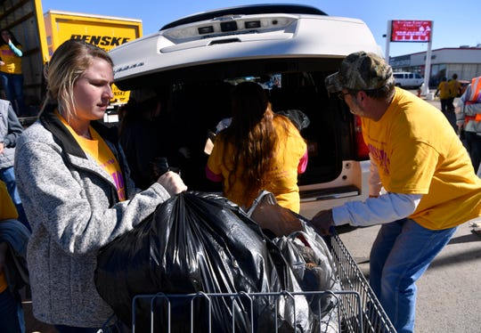 Courtney Pruett, left, helps unload a car during Mission: Thanksgiving Friday, Nov. 16, 2018 at Arrow Ford.