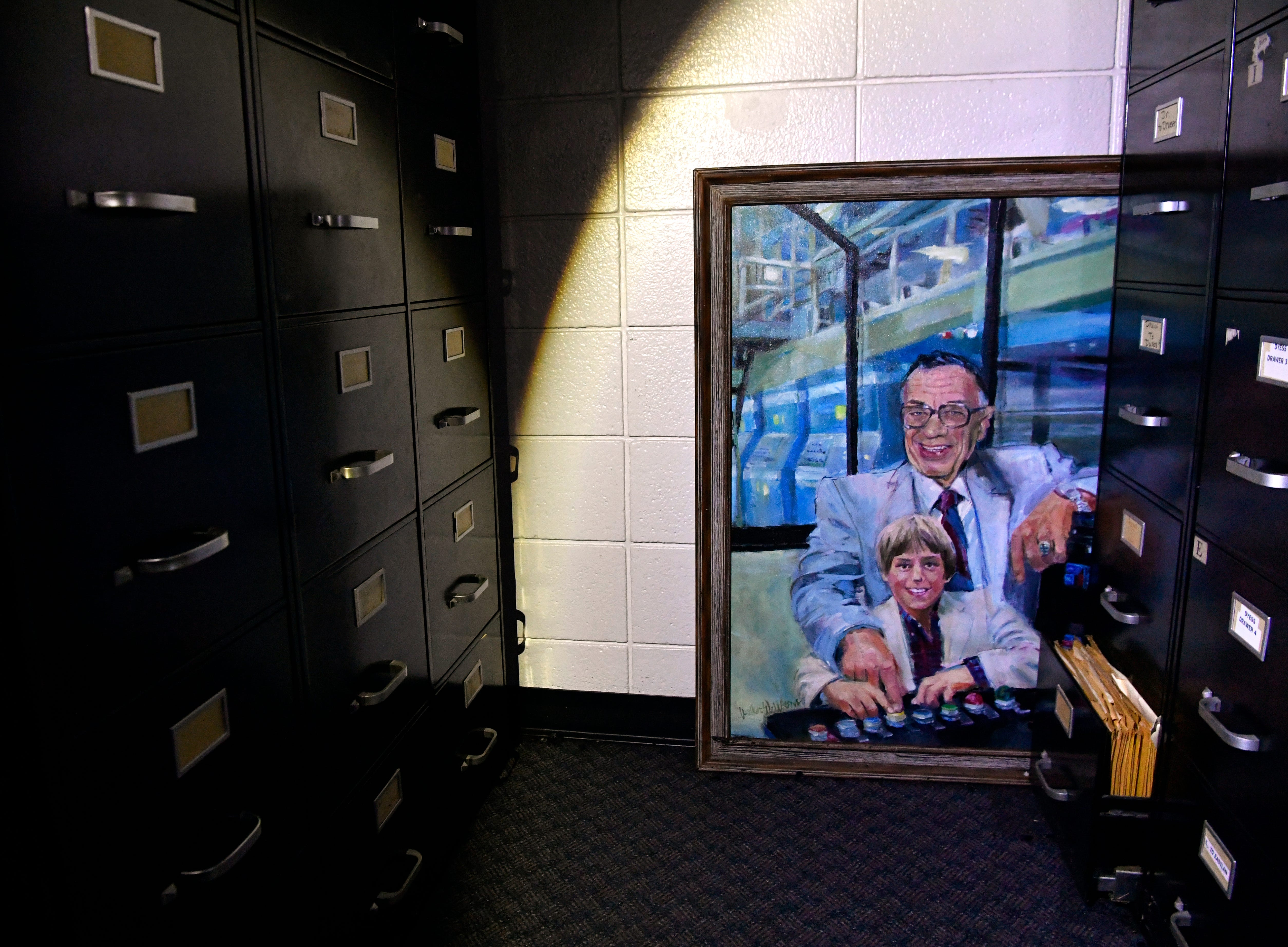 A portrait of the late Stormy Shelton, former publisher of the Abilene Reporter-News and depicting he and his grandson staring the newspaper presses, rests on the floor of the newspaper's filing area Friday. Water from Thursday's two-alarm fire had seeped up the frame of the painting but seemed to have stopped short of the canvas. Cleanup began that morning at the 137-year-old newspaper.
