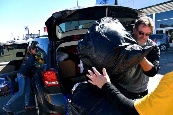 Love & Care Ministries director Mark Hewitt unloads donations from a car during Mission Thanksgiving at Arrow Ford Friday.