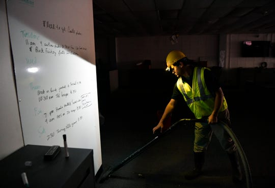 Zach Garcia with Servicemaster Restore illuminates the photo assignment job board as he vacuums water and debris in the newsroom Friday at the Abilene Reporter-News. Cleanup began in the morning at the 137-year-old newspaper after the previous day's two-alarm fire.