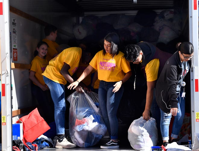 Volunteers stack donated clothes inside a truck trailer during Mission Thanksgiving Friday, Nov. 16, 2018 at Arrow Ford. The annual donation drive benefits Love & Care Ministries.