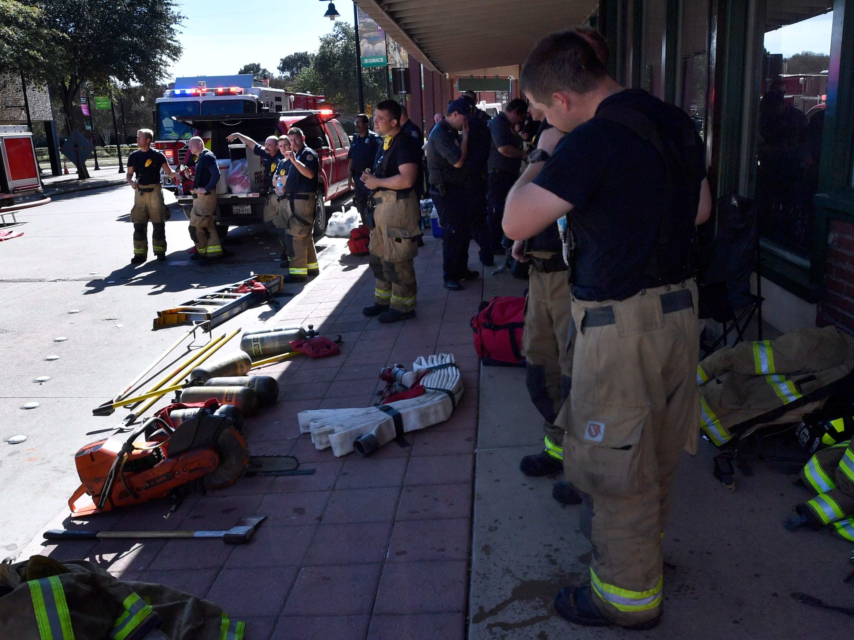 Abilene firefighters rest in front of the Grace Museum while other crews battle a two-alarm fire at the Abilene Reporter-News.