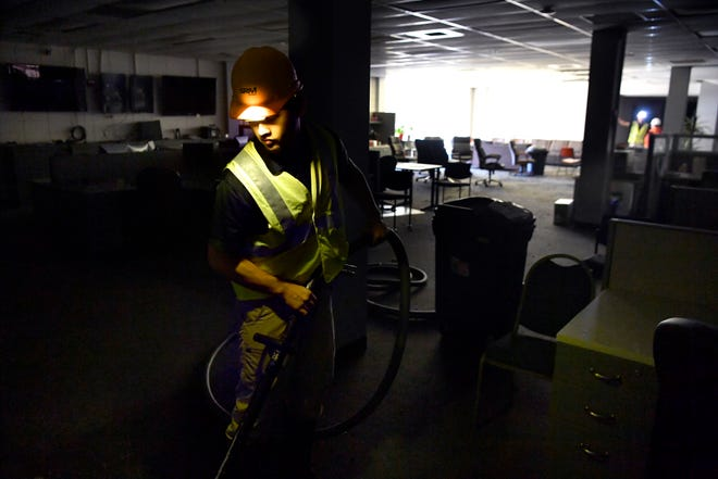 Zach Garcia with Servicemaster Restore vacuums water and debris in the newsroom Friday at the Abilene Reporter-News. Cleanup began that morning after the previous day's two-alarm fire.