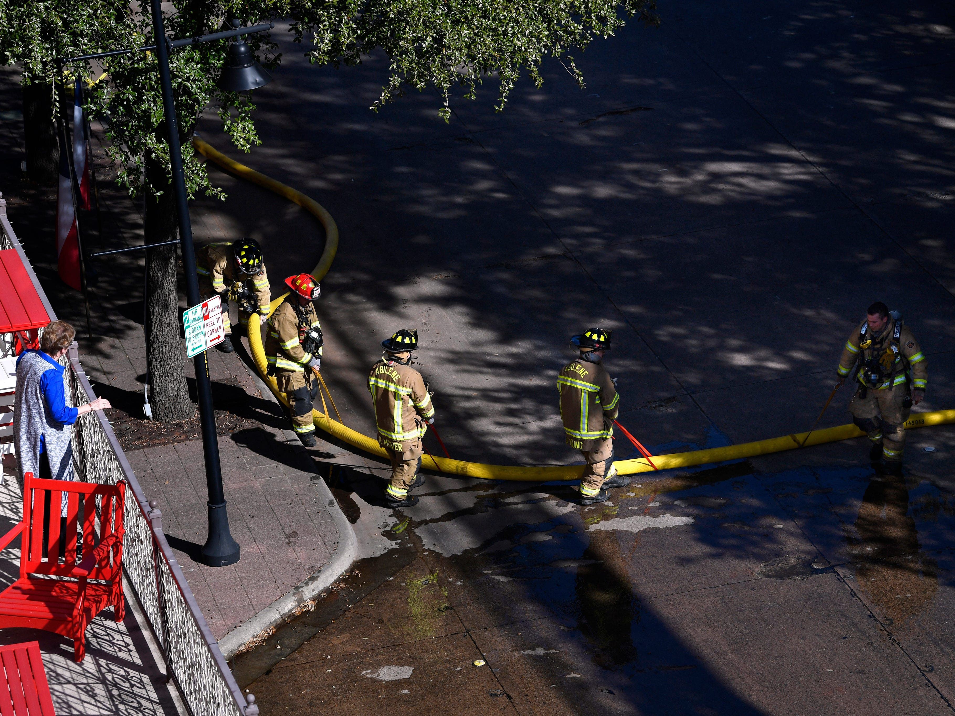 A woman watches Abilene firefighters pull a supply hose across Cypress St. as they fight a two-alarm fire at the Abilene Reporter-News Thursday Nov. 15, 2018. The fire was called in at 9:20 a.m., at one time all three of the city's ladder trucks were employed during the fight.