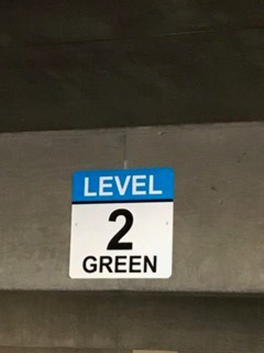 "All of the Civic Center section signs are white and blue in color, as blue is the designated color used to separate this deck from other city decks. The words, such as ""Green,"" are to help drivers remember their section."