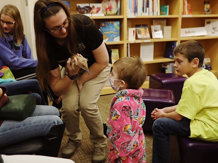 Ally Ross, an educator with the Binder Park Zoo, shows off a blue-tongued skink to Ivy Marquez, 2 at C.S. Mott Children's Hospital in Ann Arbor on Nov. 15, 2018.