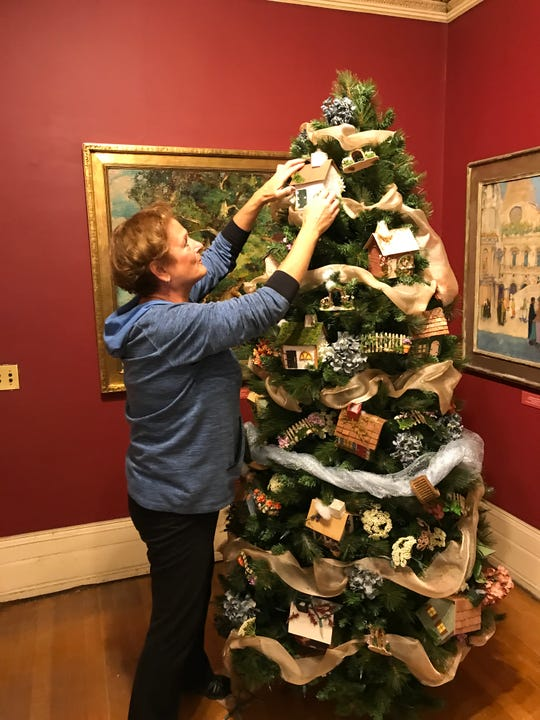 Carol Porcino adjusts her English cottage tree for Roberson Museum and Science Center's Home for the Holidays event.