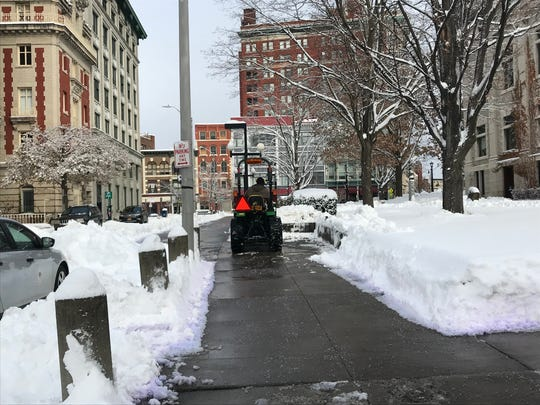 A snow plow cleans up the Collier Street sidewalk in Downtown Binghamton Friday morning.