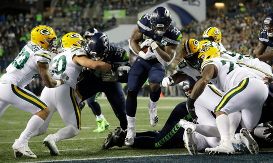 Seahawks running back Chris Carson rushes for a touchdown against the Green Bay Packers on Thursday. Seattle got significant contributions from Carson and backups Mike Davis and Rashaad Penny in the 27-24 victory.