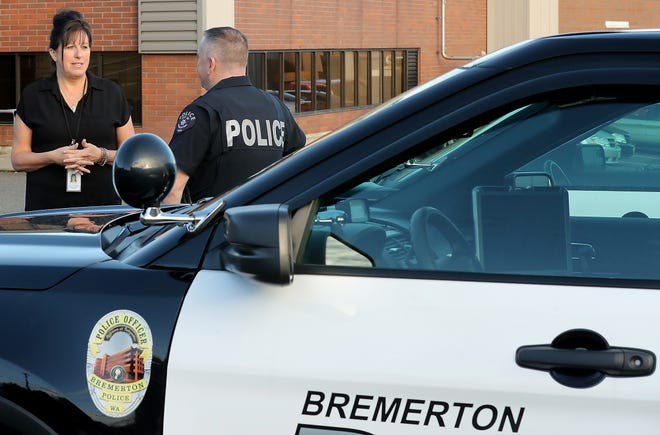 A behavioral health navigator works with an officer with the Bremerton Police Department in November 2018. Funding requests for the county's behavioral health fax include would team more mental health workers with police.