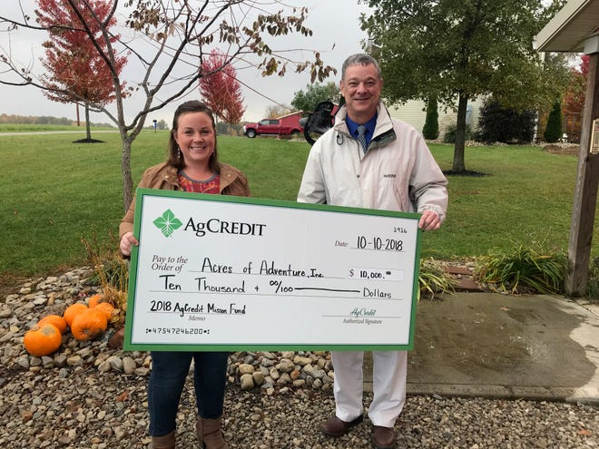 Rose Hartschuh accepts a $10,000 donation on behalf of Acres of Adventure.