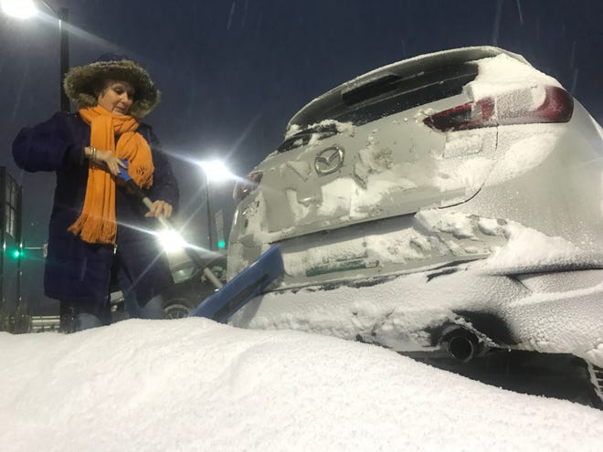 Gwen Genno of Essex, Vermont, takes a moment to clear snow from her car at the Richmond Park and Ride on Friday morning, Nov. 16, 2018, as a winter storm settled into Vermont, promising upwards of a foot of snow in some areas.