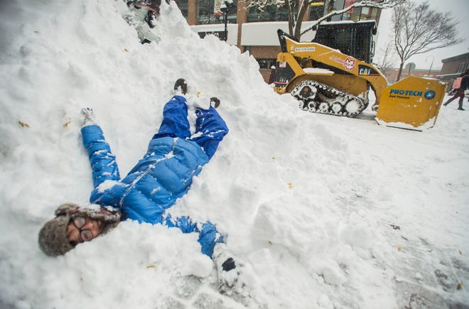Keenan Garlieb-Meno rests in a massive pile of snow on Church Street in Burlington, Vt., on Friday, Nov. 16, 2018, as a winter storm dumped more than a foot of snow in some areas on the state.