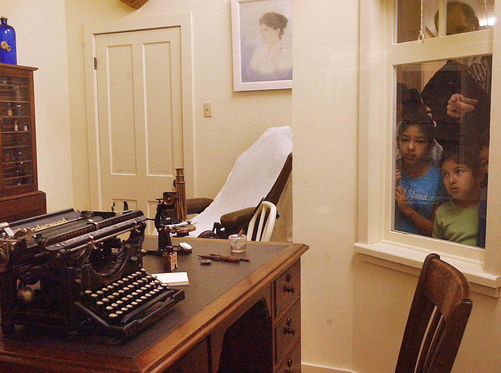 (LEFT TO RIGHT) Ashley Hinojosa (cq), 12, and Aimee Hinojosa (cq), 8, look into the replica office of 'Dr. Arthur E. Sphon' during the Christus Spohn Health Sytem 100th year celebration at the Corpus Christi Museum of Science & History on Jan. 22, 2005.