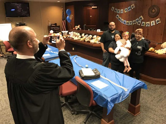 County Court-at-Law No. 5 Judge Timothy McCoy takes a photo of Ezabella Lopez and her family at Adoption Day on Nov. 16, 2018. Ezabella was one of nearly 20 children adopted.