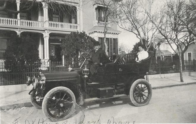 Dr. Arthur Spohn, left, with his wife's niece, Sarah Putegnat of Brownsville in Spohn's red Cadillac with a steering wheel in front of the family home at 423 N. Broadway.