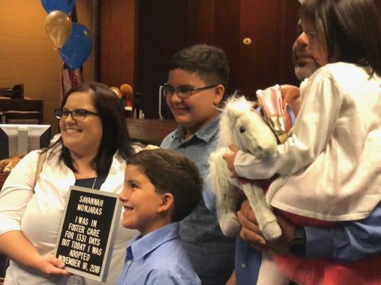 The Monjaras family smiles for a photo after their adoption of Savannah Monjaras is made official at Adoption Day on Nov. 16, 2018.