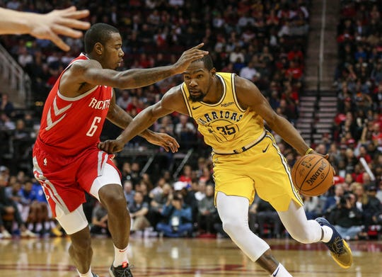 Golden State Warriors forward Kevin Durant (35) drives with the ball as Houston Rockets forward Gary Clark (6) defends during the third quarter at Toyota Center.