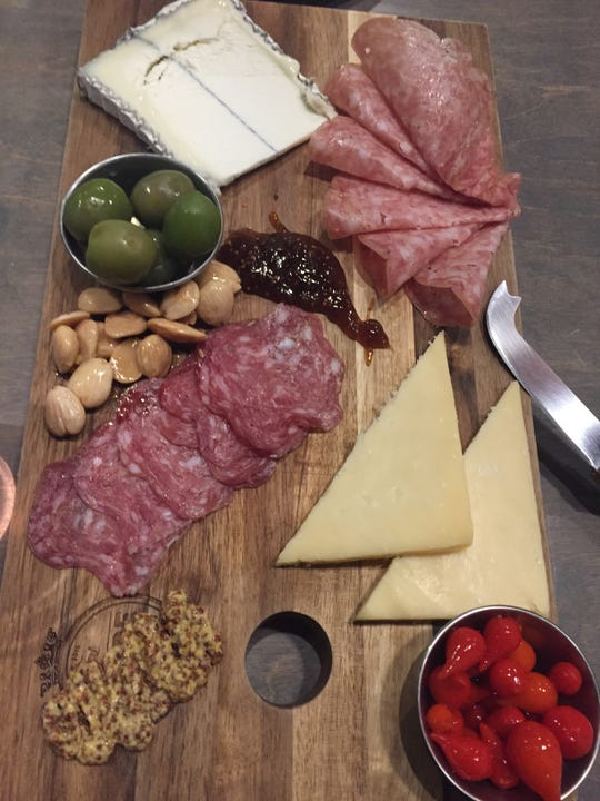 A cheese and meat board from Share includes Humboldt Fog goat cheese (top)  and Prairie Breeze cheddar, along with salami, mustard, olives, marcona almonds, fig spread and sweety drop peppers