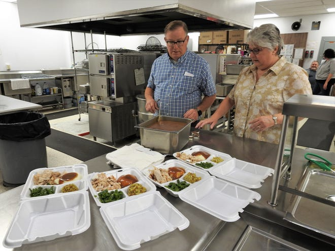 Jim and Cathy Waibel prepare carryout boxes at the annual community meal held at Coshocton High School prior to Thanksgiving. The meal is a way to give back to the community and promote community service with students. About 26 turkeys are cooked in preparation for the nearly 600 meals that are served.