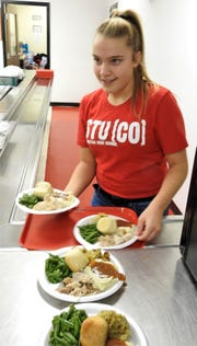 Sophomore Rylee Shrimplin takes meals from the kitchen of Coshocton High School to deliver to guests of the annual community dinner at Coshocton High School.
