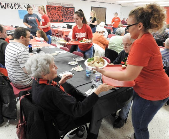 Suellen and John Husted are served by junior Lillian Whitcomb during the annual community dinner at Coshocton High School. Students from Spanish Club, Key Club, Student Council and FCCLA assisted with serving, seating and clearing tables.