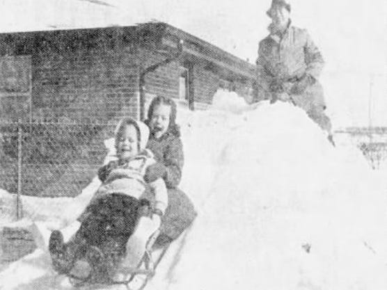 """From March 4, 1960 Des Moines Tribune: From on top of the slide he built for his little girls, Claude S. Peterson of Des Moines watches 3-year-old Laurie and 6-year-old LuAnn enjoy the ride. Peterson, a supervisor for American Telephone and Telegraph Co., worked several days to build the slide. """"My back still hurts,"""" he said."""