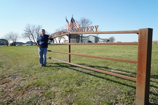 Eric Peters stands next to the gate marking the entrance to the Enterprise Cemetery. Peters, an Ankeny resident, has been investigating the cemetery's history for more than six years.