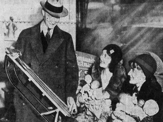 Burt Springer, left, of Des Moines shows off a sled being given away during a 1932 Christmas benefit for needy children, according to the Des Moines Tribune. Marjorie Young, center, and Mary Fiedler of the Camp Fire Girls helped with the distribution.